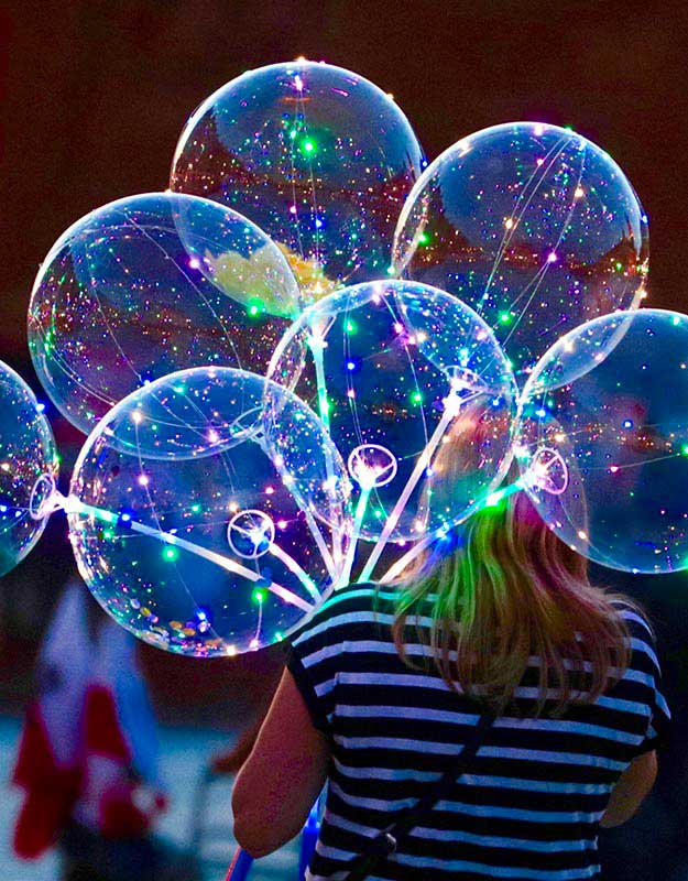 Woman with glow-in-the-dark balloons