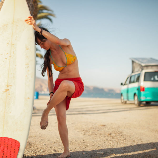 Surfer girl wiping off sand