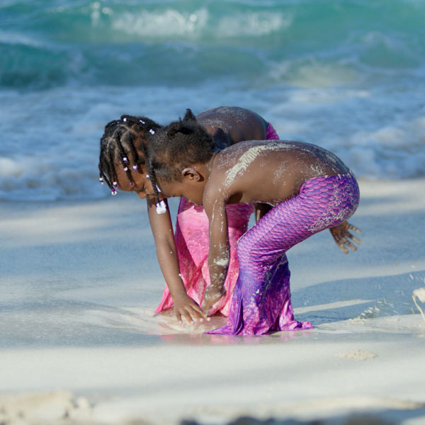 Two little mermaids digging in sand