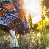 Woman in boho skirt walking through sunshine meadow