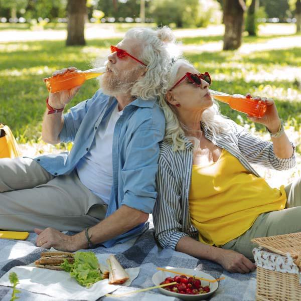 Senior man and woman drinking orange crush