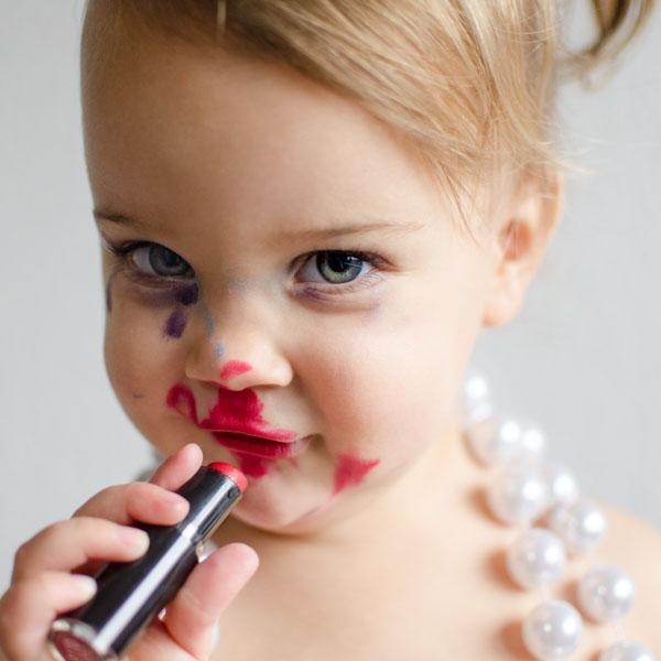 Little girl using mother's makeup