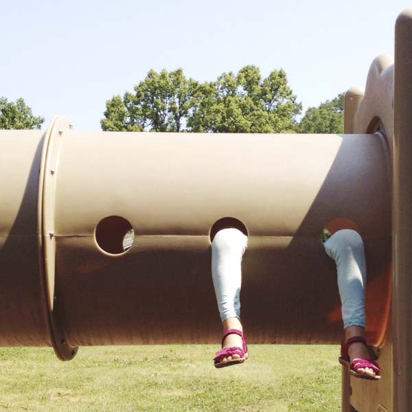 Woman hanging from playground equipment